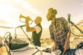 image of disc jockey  - Trendy hipster dj playing summer hits at sunset beach party with trumpet jazz performer  - JPG