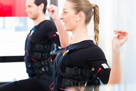 image of stimulating  - Female coach giving man and woman ems electro muscular stimulation exercise  - JPG