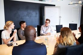 stock photo of applause  - White male executive receiving applause from colleagues during a meeting - JPG