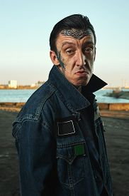 picture of hooligan  - Hooligan with tattooed Face in denim Jacket on Street making Faces - JPG
