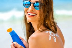 foto of sun tan lotion  - Young woman with sun shape on the shoulder holding sun cream bottle on the beach - JPG