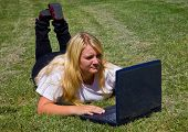 Teenager concentrates as she uses laptop outdoors