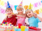 stock photo of happy birthday  - Three kids are happily posing during birthday party - JPG