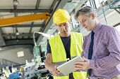 Supervisor and manual worker using digital tablet in metal industry poster