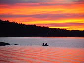 Silhouette Of A Kayak On A Lake Against Bright Sunset