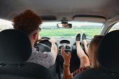 Happy Couple Enjoying On A Long Drive In A Car. Friends Driving On Road Trip On Summer Day. Caucasia poster