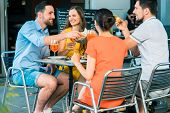 Cheerful young best friends toasting with a refreshing delicious summer drink while sitting together poster