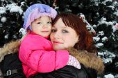 Young woman with small smiling daughter stands near green tree with snow
