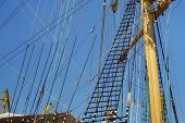 Masts Of A Sailing Ship With The Lowered Sails With Blue Sky On The Background. poster