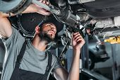 Mechanic In Overalls Repairing Car In Auto Repair Shop poster
