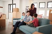 Happy Family Resting On Sofa Surrounded By Boxes In New Home On Moving Day poster