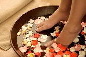 Feet dipped into spa & aromatherapy bowl