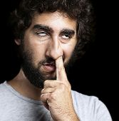 portrait of young man with the finger on his nose against a black background