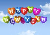 stock photo of new years celebration  - colored Happy new year heart shaped balloons floating in a blue sky - JPG