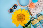 Fashion Flatlay With Sunglasses, Espaddrille Sandals, Straw Bag And Bright Big Yellow Sunflower On B poster