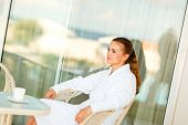 Serious Attractive Female In Bathrobe Sitting At Table On Terrace With Cup Of Coffee