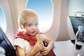 Charming Kid Traveling By An Airplane. Little Boy Drinking Water And Eating Snack During The Flight. poster