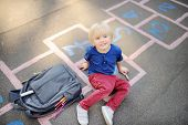 Cute Blond Boy Doing Homework Sitting On School Yard After School With Bags Laying Near. Back To Sch poster