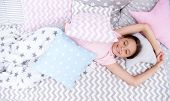 Pleasant Awakening. Girl Smiling Happy Child Lay On Bed With Star Pattern Pillows And Cute Plaid In  poster