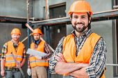 Handsome Smiling Builder Standing At Construction Site With Crossed Arms While His Colleagues Standi poster