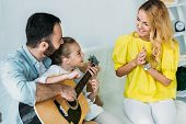Father And Daughter Playing Guitar For Mother At Home While She Clapping poster