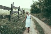 Woman walking alone on dirt road poster