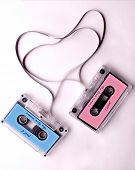 two isolated audio cassette with tape in the shape of hearts