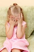Little Child A Girl In Pink Dress Sitting On Sofa In Domestic Room And Closes Face By Hands.