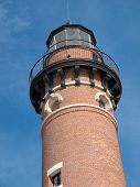 stock photo of mear  - The black parapet at the top of the red brick tower of the Little Sable Point Lighthouse circles the lantern room - JPG