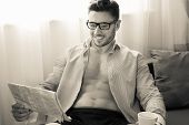 Man With Open Shirt And Pecs And Abs Sits By Window Reading The Newspaper And Drinking Coffee poster