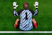 Overhead photo of a football goalkeeper standing on the goal line in ready position to face a penalt