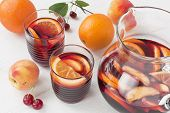 Refreshing Red Wine Sangria Summer Drink In Glasses With Orange Fruit And Peach On White Wooden Back poster