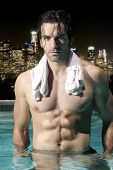 Sexy male model with great abs and muscular body in swimming pool at night with city skyline backgro