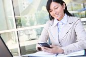 stock photo of young adult  - A young beautiful asian business woman with pda organizer - JPG