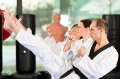 Leute im Fitnessstudio beim Training von Kampfsport, es geht um Taekwondo, der Trainer hat den schwa
