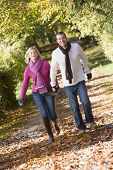 Couple Outdoors Running On Path In Park Holding Hands Smiling