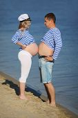 Wife and husband comparing bellies