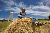 Contended Young Farmer Sitting On Round Bale Of Harvested Hay