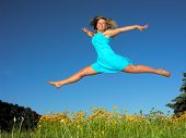 Teenage Girl Jumping In The Meadow