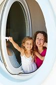 Smiling mother and her little daughter look out from window made as porthole
