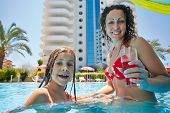 Mother with glass of beverage and her daughter hide under umbrella from sun in pool