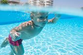 A boy swimming under water in the pool of hotel