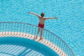 Boy sunbathing on the edge of the pool raised his hands up
