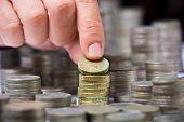 Closeup de pilha de moedas da libra britânica com uma mão masculina