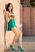 pic of leggy  - Alluring young leggy brunette posing near the wall outdoors - JPG
