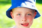 Cute Little Boy Wearing A Sun Hat In The Garden Sticking Out Tounge