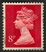 UK-CIRCA 1973:A stamp printed in UK shows image of Elizabeth II is the constitutional monarch of 16 sovereign states known as the Commonwealth realms, in red, circa 1973.