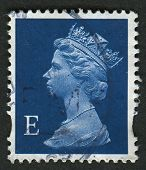 UK-CIRCA 2002:A stamp printed in UK shows image of Elizabeth II is the constitutional monarch of 16 sovereign states known as the Commonwealth realms, in blue, circa 2002.