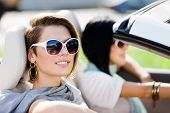 Close up of girls wearing sunglasses in the convertible car. Little holiday trip of friends