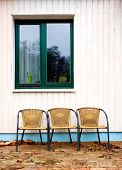 Three Chairs Against White Wall And Green Window